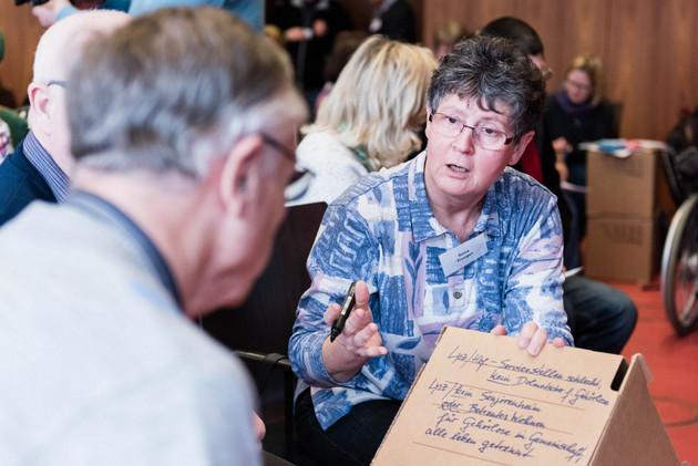 Ein Mann und eine Frau sind im Gespräch. Die Frau redet und hält einen Stift und eine Pappe mit handschriftlichen Notizen in den Händen.