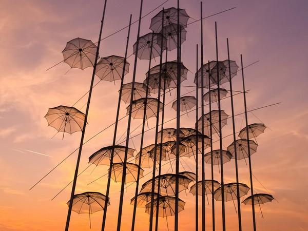 Kunstinstallation mit metallenen Schirmen vor dem Abendhimmel.
