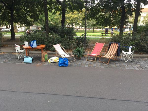 Auf einem Parkstreifen stehen verschiedene Liegestühle und ein Tisch beim Parking Day