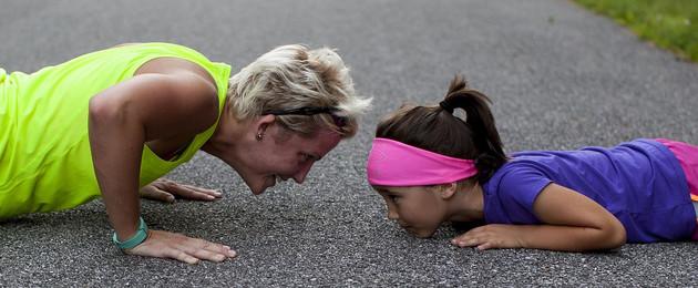 Mutter und Tochter machen Liegestütze auf der Straße