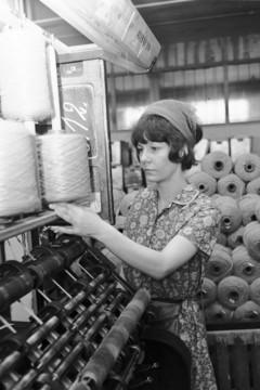 Bild wird vergrößert: Arbeiterin an einer Maschine mit Stoffspindeln