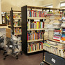 Ein Bücherwagen mit Bücherstapeln steht in der Bibliothek Plagwitz vor neuen Regalen, daneben zwei in Folie eingepackte Drehsessel.