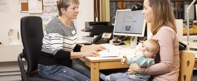 Eine mit dem Baby auf dem Schoß und eine weitere Frau ihr gegenüber sitzen an einem Schreibtisch in einem Büro.