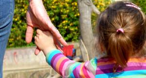 Ein kleines Kind hält die Hand eines Erwachsenen