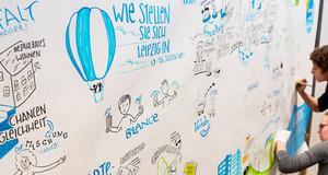 zwei Künstlerinnen notieren die Ergebnisse des Beteiligungsprozesses mittels grafic recordning auf einer Wandzeitung
