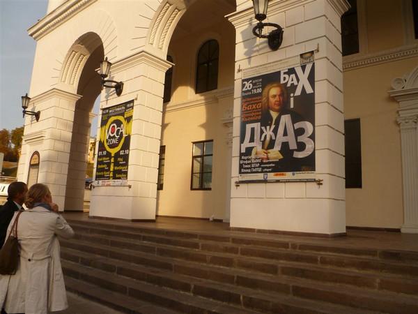 Gebäudeeingang aus Rundbögen, an denen ein Plakat mit dem Konterfei Bachs zur Bewerbung der Veranstaltung angebracht ist