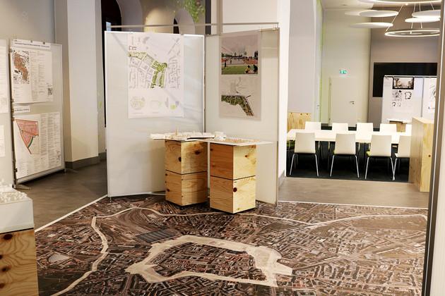 Blick in das Stadtbüro. Im Vordergrund eine Ausstellung von Architekturskizzen und Modellen.