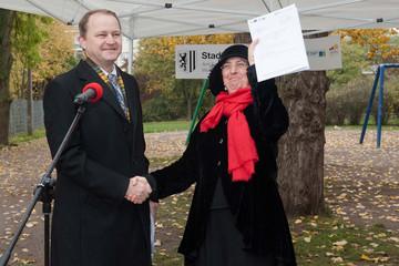 Bild wird vergrößert: Baubürgermeisterin Dorothee Dubrau erhält den Bescheid von einem Vetreter des Sächsischen Innenministeriums und hält diesen in die Luft