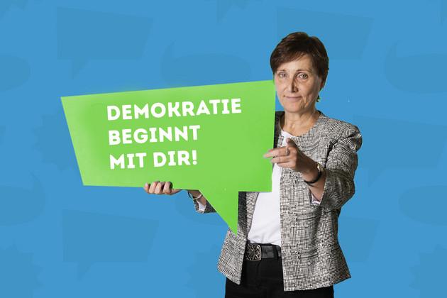"""Die Stadträtin Beate Ehms hält ein Schild mit dem Statement """"Demokratie beginnt mit Dir.""""."""