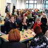 ca. fünfzig Menschen diskutieren an Tischen