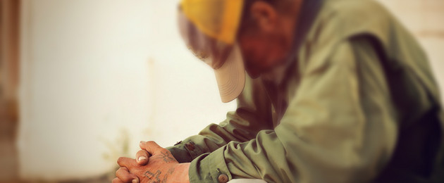 Obdachloser Mensch sitzt mit nach unten geneigten Kopf