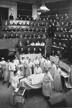 Bild wird vergrößert: Szene aus dem Hörsaal mit Studenten und Lehrkräften bei einer chirurgischen Lehroperation im Jahre 1900.