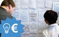 Ein Mann und eine Frau stehen vor einer Pinnwand mit Post-its zu geplanten Projekten. Dazu eine Grafik mit einem Euro-Zeichen und einer Glühbirne.