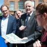 Horst Seehofer und Burkhard Jung umringt von Menschen. Herr Seehofer hält ein handschriftliches Plakat in der Hand.