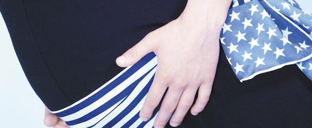Eine schwangere Frau hält sanft ihre Hände an den Babybauch.