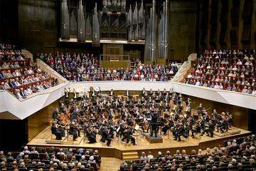 Bild wird vergrößert: Blick auf die Bühne des Gewandhaues auf dem oberen Rang des vollbesetzten Hauses. Auf der Bühne ist das Orchester in großer Besetzung in Konzertatmosphäre zu sehen