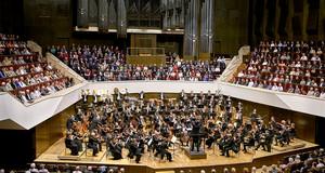 Blick auf die Bühne des Gewandhaues auf dem oberen Rang des vollbesetzten Hauses. Auf der Bühne ist das Orchester in großer Besetzung in Konzertatmosphäre zu sehen