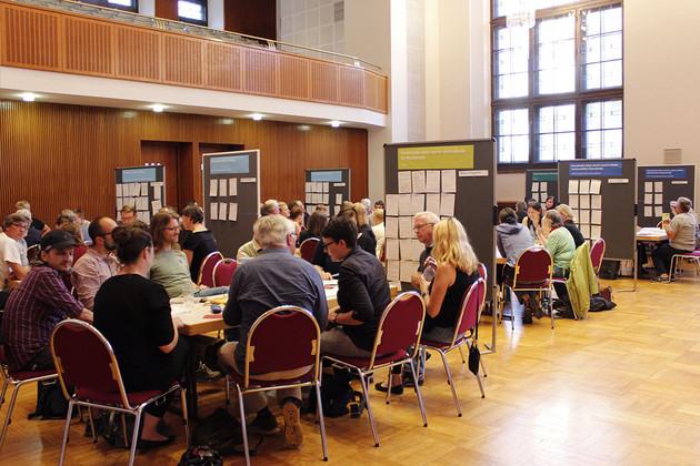 Menschen diskutieren an verschiedenen Tischen in Gruppen miteinander