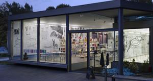 Außenansicht der Galerie für Zeitgenössische Kunst während der blauen Stunde. Durch die großen Glasscheiben sind beleuchtete Räume sichtbar.