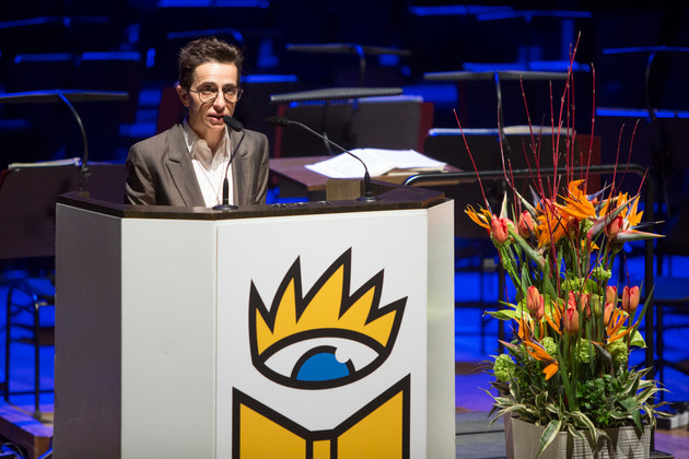 Masha Gessen speaking at a speaker's desk