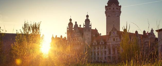 Der Sonnenaufgang blitzt hinter dem Neuen Rathaus hervor.