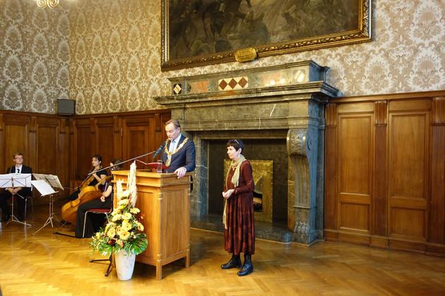 Oberbürgermeister Burkhard Jung steht hinter einem Stehpult und liest eine Rede vor. Neben ihm steht die Preisträgerin Dr. Heide Steer.