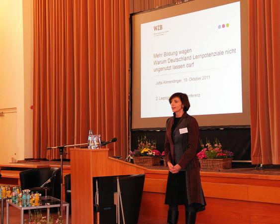 Frau Jutta Allmendinger steht, einen Vortrag haltend, am Podium. Der Raum ist leicht abgedunkelt. Auf einer Projektionsfläche hinter ihr erscheinen begleitende Texte und Diagramme.