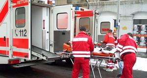 Sanitäter von Feuerwehr und Arbeiter-Samariter-Bund schieben einen Verletzten auf einer Rolltrage zum Rettungswagen.