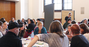 Viele Menschen an mehreren Tischen bei Diskussionsrunden in einem Raum des Neuen Rathauses.