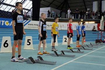Bild wird vergrößert: Mehrere Jungs in Sportbekleidung stehen vor ihren Startblöcken an der Rennbahn in der Arena Leipzig.