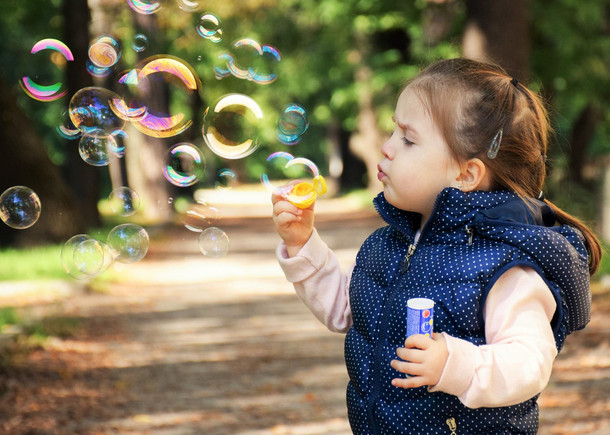 Kleinkind steht auf einem Wanderweg und pustet Seifenblasen in die Luft.