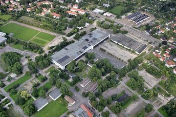 Bild wird vergrößert: Luftaufnahme des agra-Geländes: zu sehen Hallen, leere Plätze und kleinere Grünflächen, sowie Bäume