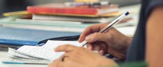 Hände die etwas in ein Notizbuch schreiben