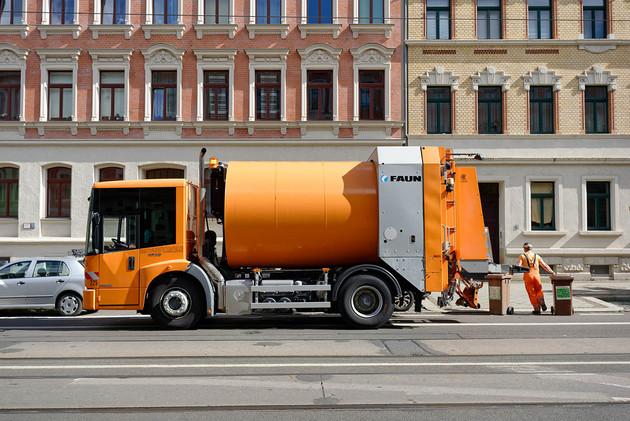 Ein Abfallsammelfahrzeug der Stadtreinigung steht an einer Straße. Ein Mitarbeiter zieht zwei Biotonnen zum Gehweg.