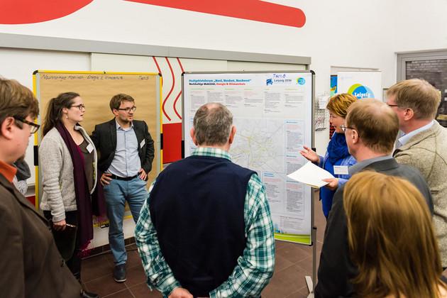 Ein Mann hält einen Vortrag vor einer Moderationswand, eine kleine Gruppe von Menschen steht im Halbkreis und hört zu.