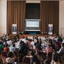 Saal voller menschen, die an Tischen sitzen und eine Präsentation auf einer Leinwand anschauen
