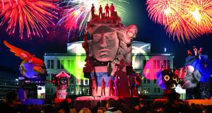 Visualisierung mehrerer überlebensgroßer Skulpturen zum Stadtfestspiel auf dem Augustusplatz. Eine Menschenmenge schaut zu. Ein Feuerwerk ist am Himmerl.