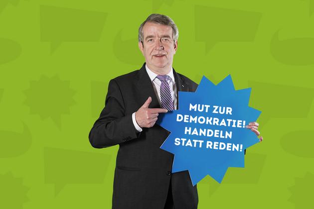 """Der Stadtrat Christian Kriegel hält ein Schild mit dem Statement """"Mut zur Demokratie! Handeln statt reden!""""."""