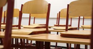 Leeres Klassenzimmer mit auf die Tische hochgestellten Stühlen