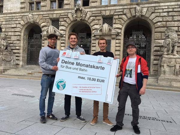 Vier Mitglieder des Jugendparlamentes vor dem Neuen Rathaus. In ihren Händen ein großes Schild: Deine Monatskarte für Bus und Bahn maximal 10 Euro.
