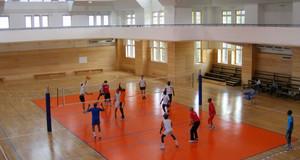 Zwei Mannschaften spielen Volleyball gegeneinander in einer Sporthalle.