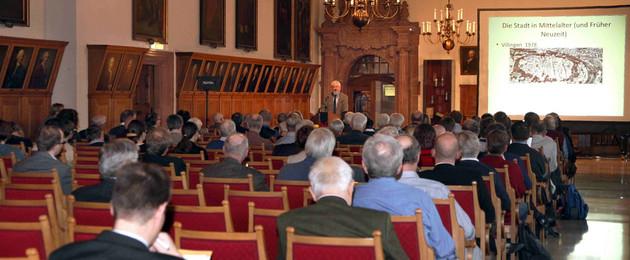 Teilnehmer des Tages der Stadtgeschichte, die im Festsaal des Alten Rathauses sitzen. Zu sehen ist auch der Referent Professor Dr. Enno Bünz, der einen Vortrag hält.