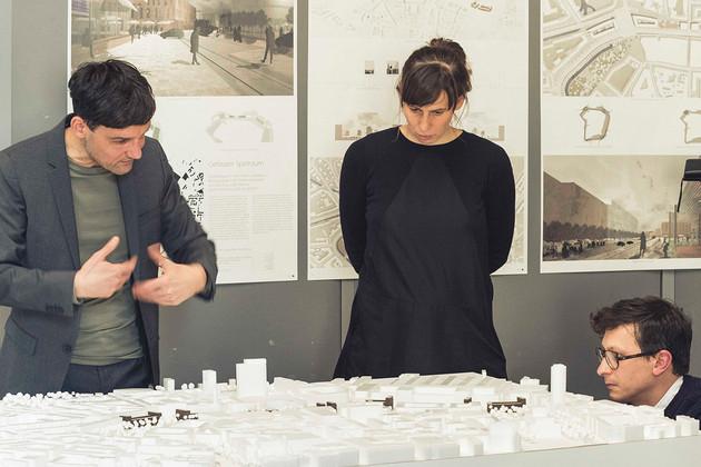 Zwei Männer und eine Frau schauen auf ein Stadtmodell und diskutieren.