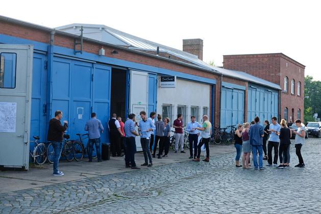 Eine Gruppe von Menschen steht vor einem blauen, eingeschossigen, Haus