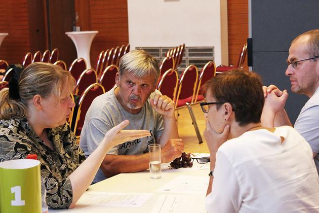 Vier Menschen diskutieren an einem Tisch miteinander