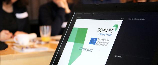 Ein Monitor der DEMO EC anzeigt und dahinter sitzende Menschen