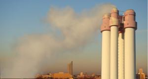 Rauchende Schornsteine einer fabrik, Silhouette von Leipzig im Hintergrund