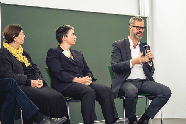 Zwei Frauen und ein Mann sitzen auf Stühlen auf einer Bühne, der Mann spricht in ein Mikrofon.