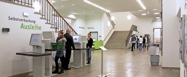 Foyer des Erdgeschosses der Leipziger Stadtbibliothek, Kunden stehen an Selbstverbuchungs-Automaten und entleihen Medien
