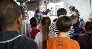 Kinder stehen im Heizungskeller um einen Hausmeister herum. Er erklärt ihnen die Funktion der Heizungsanlage.